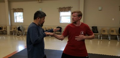 Master Chen showing Rick Pietila how to align the rear elbow with the front hand